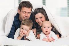 Lycklig familj med barn i säng arkivbild