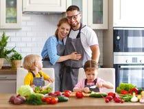 Lycklig familj med barn som förbereder grönsaksallad arkivbild