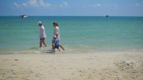 Lycklig familj med barn som går på den sandiga stranden Tropisk ö, på en varm dag stock video