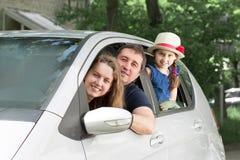 Lycklig familj med barn som sitter i en familjebil arkivfoton