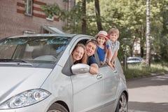 Lycklig familj med barn som sitter i en familjebil royaltyfri foto