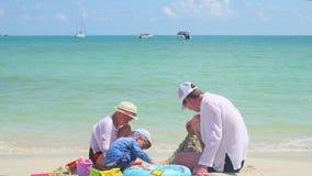 Lycklig familj med barn som spelar på den sandiga stranden med leksaker Tropisk ö, på en varm dag stock video