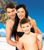 Lycklig familj med barnet på den tropiska stranden Arkivbild