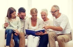 Lycklig familj med bok- eller fotoalbumet hemma Arkivfoton