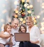 Lycklig familj med den bärbar datordatoren och kreditkorten Arkivbilder