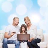 Lycklig familj med den bärbar datordatoren och kreditkorten Arkivfoton