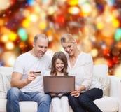 Lycklig familj med den bärbar datordatoren och kreditkorten Royaltyfri Foto