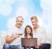 Lycklig familj med den bärbar datordatoren och kreditkorten Arkivbild