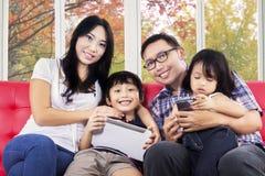 Lycklig familj med den hemmastadda digitala minnestavlan Royaltyfri Bild