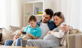 Lycklig familj med den hemmastadda smartphonen arkivfoton