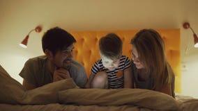 Lycklig familj med den lilla sonen som lär att spela minnestavladatoren som hemma ligger i säng i afton lager videofilmer