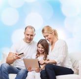 Lycklig familj med den minnestavlaPC och kreditkorten Fotografering för Bildbyråer