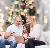Lycklig familj med den minnestavlaPC och kreditkorten Arkivfoton