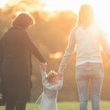 Lycklig familj med den utomhus- modern, dottern och mormodern Solnedgång i parkera Royaltyfri Foto