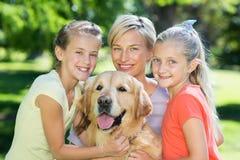 Lycklig familj med deras hund Arkivbild