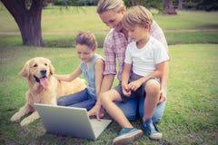 Lycklig familj med deras hund genom att använda bärbara datorn Arkivfoto
