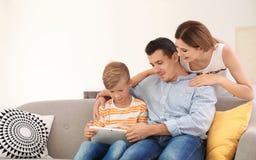 Lycklig familj med det gulliga barnet som använder minnestavlan royaltyfri foto