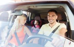Lycklig familj med det lilla barnet som kör i bil arkivbilder
