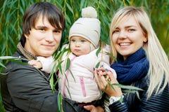 Lycklig familj med dottern på bakgrund av gröna träd Royaltyfria Foton