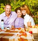 Lycklig familj med dottern på höstpicknick Arkivfoton