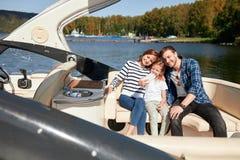 Lycklig familj med dottern på segelbåten på den soliga höstdagen arkivbilder