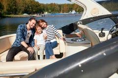 Lycklig familj med dottern på segelbåten på den soliga höstdagen royaltyfri fotografi