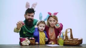 Lycklig familj med easter ägg Lycklig familj som förbereder sig för påsk Fader, moder och deras iklädda hareöron för son arkivfilmer