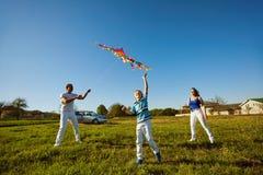 Lycklig familj med en drake som spelar i fältet i natur royaltyfria foton