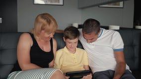 Lycklig familj med en minnestavla på soffan Föräldrar med ett barn förbindelse till en digital minnestavla stock video
