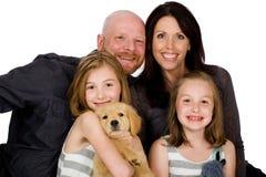 Lycklig familj med en valp Royaltyfri Fotografi