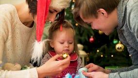 Lycklig familj med ett barn att spendera jul tillsammans Föräldrar och dotterlek hemma nära julgranen royaltyfri fotografi