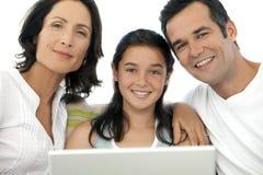 Lycklig familj med ett barn som använder bärbara datorn Royaltyfria Bilder