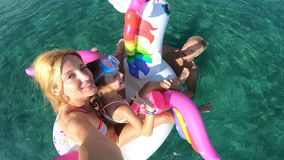 Lycklig familj med flickan som tar selfie i havsplaceringen på den uppblåsbara enhörningen arkivfilmer
