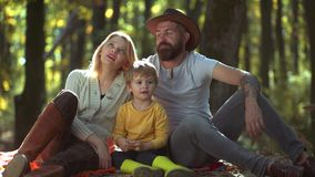 Lycklig familj med gossebarn Unga föräldrar och barn som har picknicken och tillsammans kopplar av på en solig dag för höstar stock video
