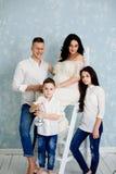 Lycklig familj med gravida kvinnan och barn som poserar i studion arkivfoto