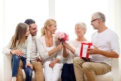 Lycklig familj med grupp- och gåvaasken hemma fotografering för bildbyråer