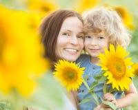 Lycklig familj med härliga solrosor Royaltyfri Foto