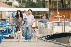 Lycklig familj med hundkapplöpning på kajen i sommaren Arkivbild