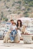 Lycklig familj med hundkapplöpning på kajen i sommaren Arkivfoton