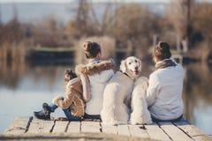Lycklig familj med husdjur nära sjön Arkivbild