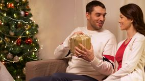Lycklig familj med julgåva hemma arkivfilmer