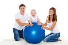 Lycklig familj med konditionbollen. Arkivbild
