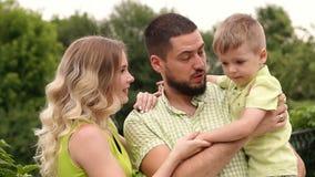 Lycklig familj med lite sonen i parkera stock video