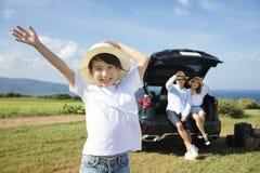Lycklig familj med liten flickalopp med bilen royaltyfri fotografi