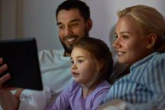 Lycklig familj med minnestavlaPC i säng hemma Arkivbild