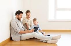 Lycklig familj med minnestavlaPC:n som flyttar sig till det nya hemmet royaltyfria foton