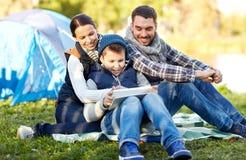 Lycklig familj med minnestavlaPC och tält på campingplatsen arkivbilder