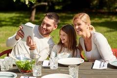 Lycklig familj med minnestavlaPC på tabellen i trädgård Royaltyfri Fotografi