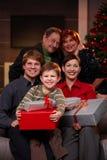 Lycklig familj med morföräldrar på jul Arkivfoto