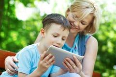 Lycklig familj med ny teknik arkivbild